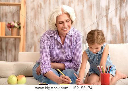Happy grandmother is drawing with her granddaughter at home. They are sitting on couch and smiling