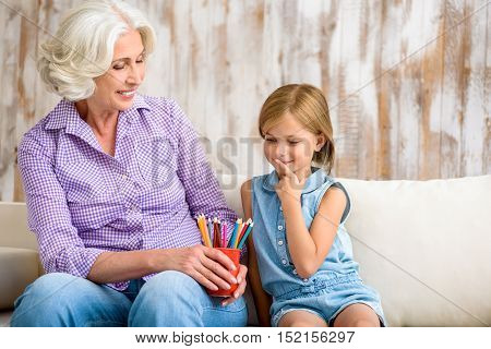 Lets draw together. Joyful grandmother is giving pencils to her granddaughter and smiling. Girl is sitting on sofa and choosing pencil with concentration