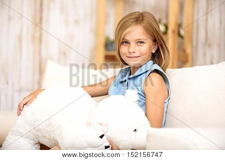 Joyful little girl is playing with teddy bear at home. She is sitting on sofa and smiling