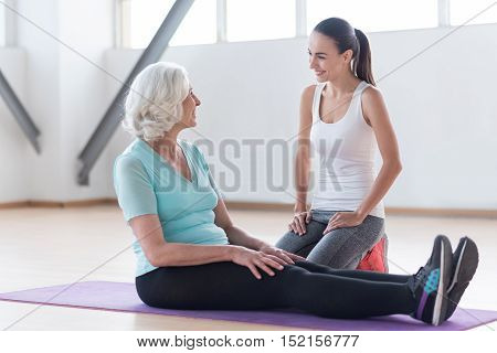 Together it is more interesting. Good looking delighted active woman looking at each other and smiling while having fitness training