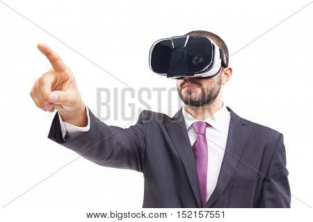 Young business man with VR glasses pointing at copyspace, isolated on white background