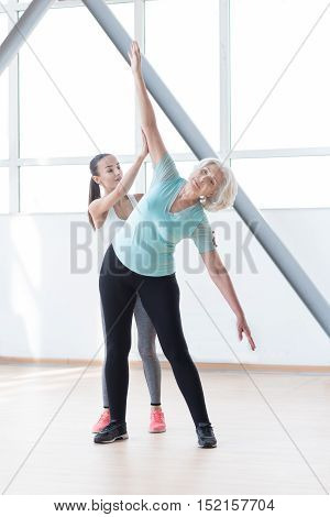 Having aerobics classes. Well built serious confident woman stretching out her hands and bending to the left while training in a fitness club