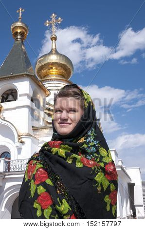 The girl in the painted head scarf standing against the blue sky Church