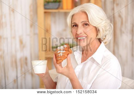 Relaxed old woman is eating croissant and drinking tea at home. She is looking at camera and smiling