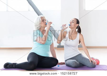 Prevent dehydration. Good looking pleasant thirsty woman holding plastic bottles and drinking water while sitting in a gym hall