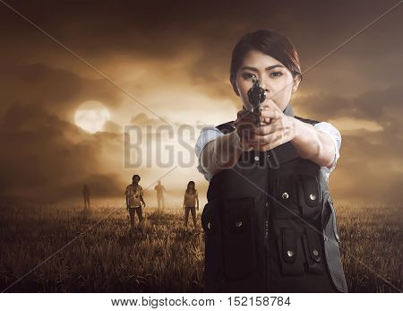 Asian Woman With Vest Holding Pistol On The Meadow