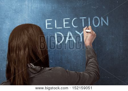 Beauty woman writing a 'ELECTION DAY' on blue chalkboard. Election day background or concept