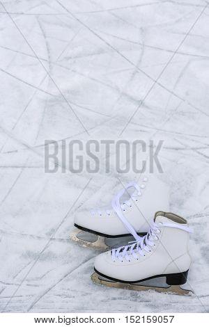 I love ice skating. Ice skates on rink background.