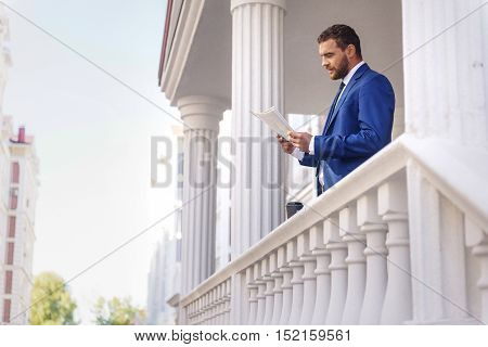 handsome guy in costume reading newspaper outdoors with copy space