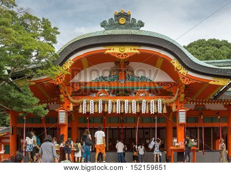Kyoto Japan - September 17 2016: People gather in front of the main vermilion shrine at Fushimi Inari Taisha Shinto Shrine. They appeal and pray to the spirits of ancestors. Gray roof with golden trim. Cloudy sky and green trees.