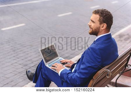 man sitting with notebook on his knees and looking away, outdoors