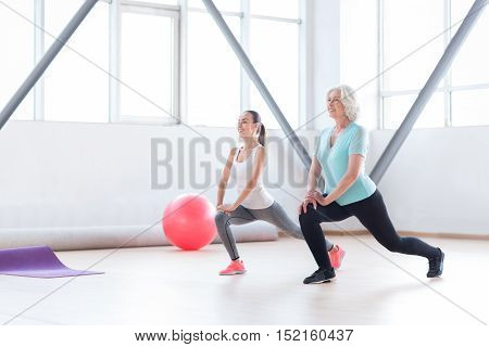 Hard work and persistence. Good looking cheerful persistent women doing physical exercises and smiling while having fitness classes