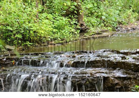 A waterfall in the woods during summer