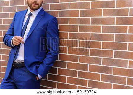 elegant smart man thinking in an expensive suit on the street with copy space, success and business concept