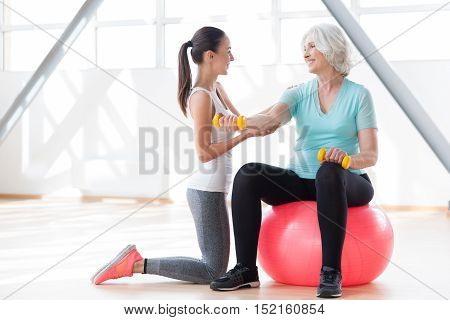 Working with people. Positive skilled slender coach holding a hand of the woman and looking at her while having a fitness class