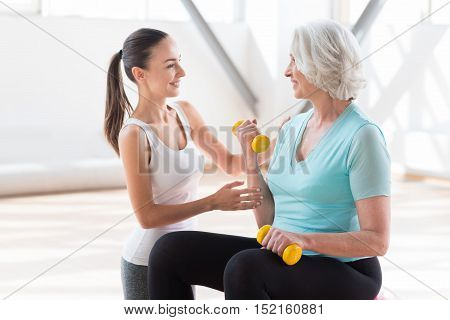 Let me help you. Positive skilled female coach standing near the woman and looking at her while helping her during the workout