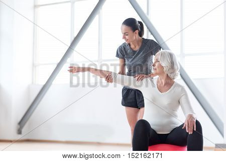 Towards the healthy way of life. Nice thoughtful good looking woman stretching out her arm and looking at it while sitting on a fitness ball