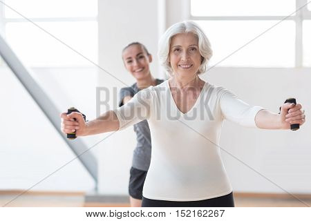 Keeping fit. Optimistic joyful nice woman looking at you and smiling while standing in front of her couch
