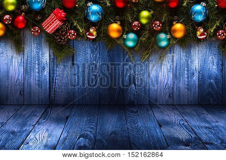 2017 Happy New Year seasonal background with real wood green pine, colorful Christmas baubles, gift boxe and other seasonal stuff over an old wooden aged background