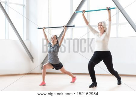 Concentrated on the activity. Hard working sporty good looking women holding plastic sticks and doing an exercise while being in a gym