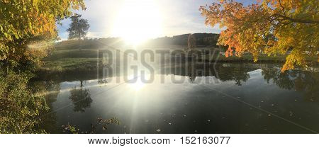 landscape photo of pond and fall foliage