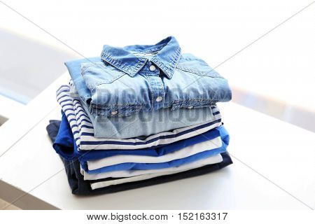 Pile of clothes on white table, closeup