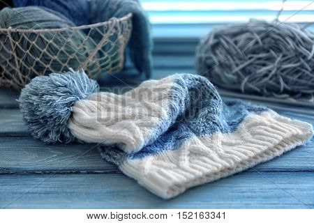 Knitted cap with yarn and metal basket on wooden background
