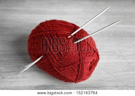 Ball of red knitting yarn and needles on grey wooden background