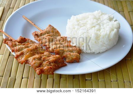 grilled pork stab in wooden stick eat couple with plain rice