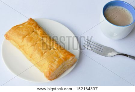 chicken pie with fork and coffee cup on white paper