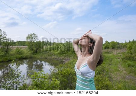 Girl put her hands on her forehead against the backdrop of beautiful scenery
