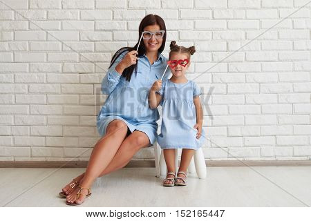 Face of young mother and her cute daughter beamed with joyful emotions while posing at camera and holding paper glasses on sticks