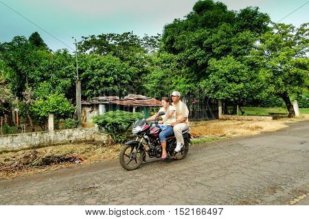 La maquina, Guatemala - June 16, 2011: Couple on a motor bike on a dirt road in La maquina, Guatemala. Editorial use only.