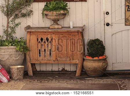 Rustic garden potting table in an outside living area with a decorative rug and plants