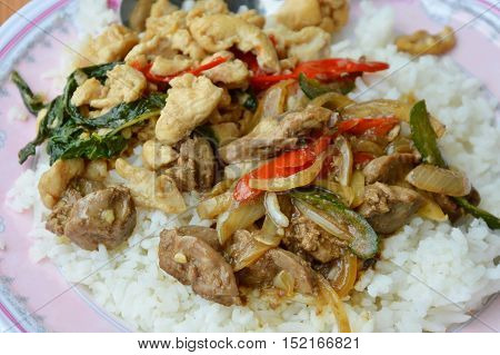 spicy stir fried chicken meat and entrails with basil leaf on rice