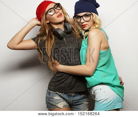 life style, happiness, emotional and people concept: Close up fashion lifestyle portrait of two young hipster girls best friends, wearing bright make up and similar trendy hats, making funny faces.