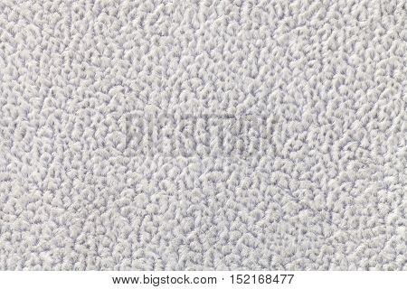 Light gray fluffy background of soft fleecy cloth. Texture of textile closeup.