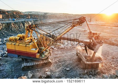 Mining. excavator loading granite or ore into dump truck