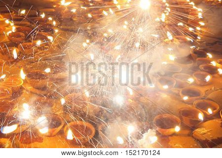 An abstract Diwali background of fireworks and sparklers on traditional lamps.