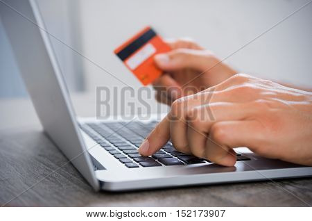 Closeup hand of man typing credit card details on laptop to complete payment process. Close up of male hand paying bills online with laptop and credit card. Internet banking. Man using laptop.