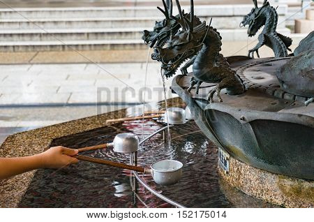 Person filling up ladle with water of chozuya fountain. Traditional Japanese Shinto washbasing for ritual cleansing of worshippers at the entrance to holy places. Senso-ji Asakusa Tokyo Japan