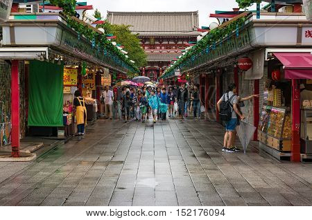 Tokyo Japan - Aug 29 2016: Tourists buying souvenirs in a shop on the street to Asakusa temple with Senso-ji temple on the background