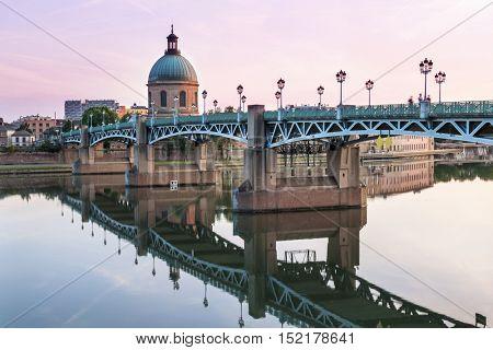 Saint-Pierre Bridge reflecting in Garonne river and Dome de la Grave at sunset in Toulouse, France