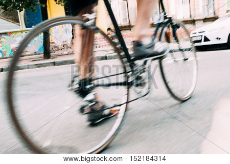 Blurry photo of male legs on bicycle. Man riding on bike on asphalt street in city. Healthy, active lifestyle
