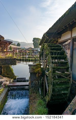 Water wheel mill in Japanese Oshino Hakkai historic village. With traditional thatch roof farmhouses on the background. Fuji Five Lakes Japan