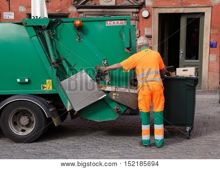 Stockholm, Sweden - June 18, 2013: A man in orange overalls empties garbage into a green garbage truck on the Main Square in the Old Town