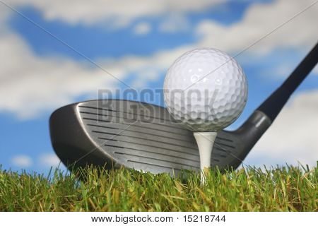 Ready to drive a golf ball with grass and sky.