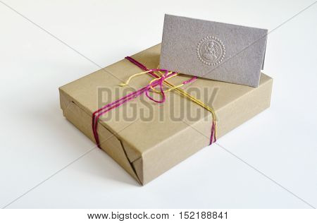 Gift box wrapped with brown paper with colored string. Festive gift pack with a greeting card on white background.