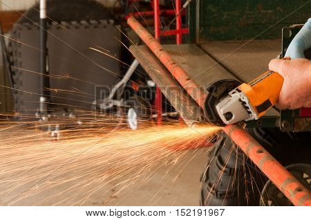 Closeup of a man using a grinder with cutoff blade to cut a section of pipe, showering sparks across the workshop