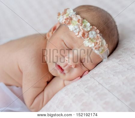 funny sleeping newborn girl with her hands under her head and headband with flowers